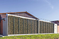 Biofilterwand gevuld met wortelhout voor de stal