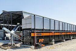 Lange container met links twee transportschroeven